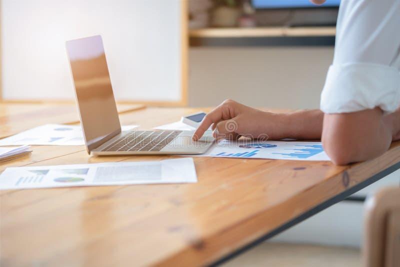 Närbild av manliga händer genom att använda bärbara datorn, mans händer som skriver på bärbar datortangentbordet, sidosikt av aff royaltyfria foton