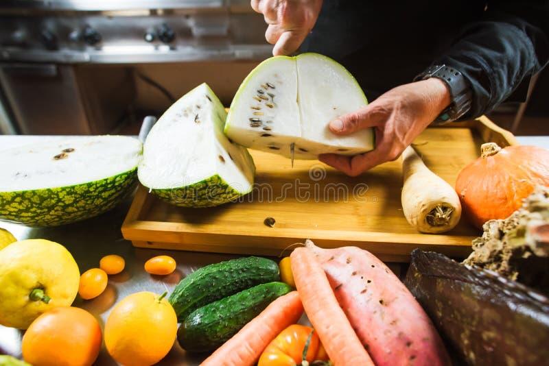 Närbild av manliga händer som klipper den vita vattenmelon arkivbild