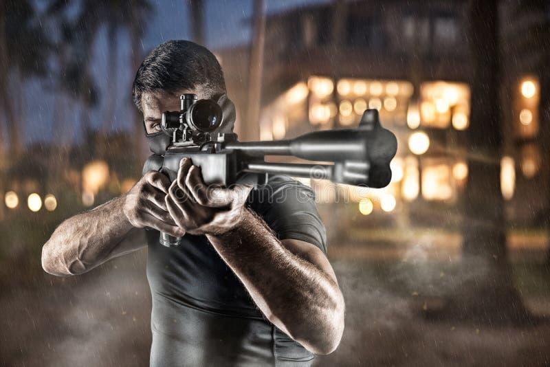 Närbild av mannen i huvudbonaden som siktar med prickskyttgeväret arkivbilder