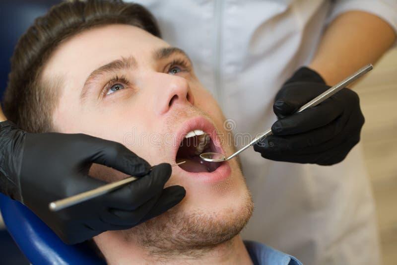 Närbild av mannen med den öppna munnen under muntlig undersökning på tandläkaren arkivbild