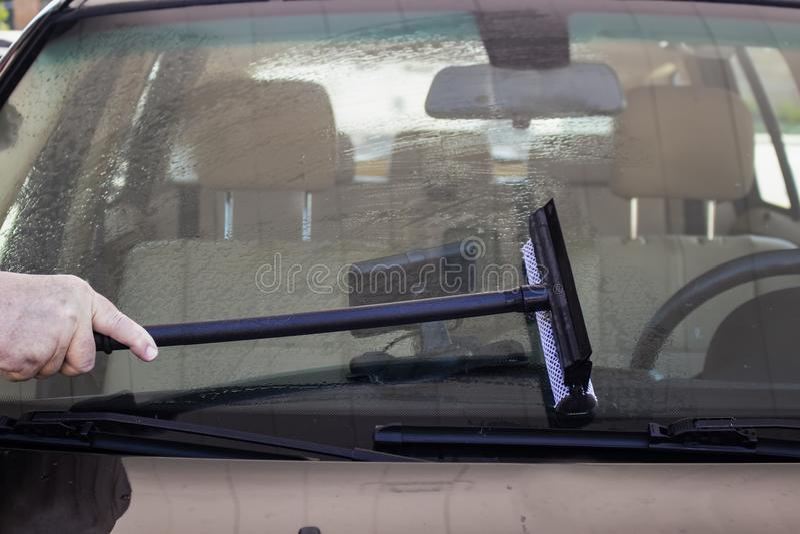 Närbild av mannen som använder skrapan för att göra ren vindrutan av en bil med GPS en synlig insida på streck royaltyfri fotografi