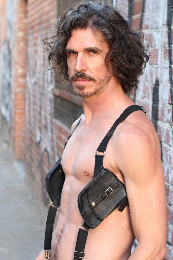 Närbild av mannen som bär den svarta fetischläderdräkten fotografering för bildbyråer