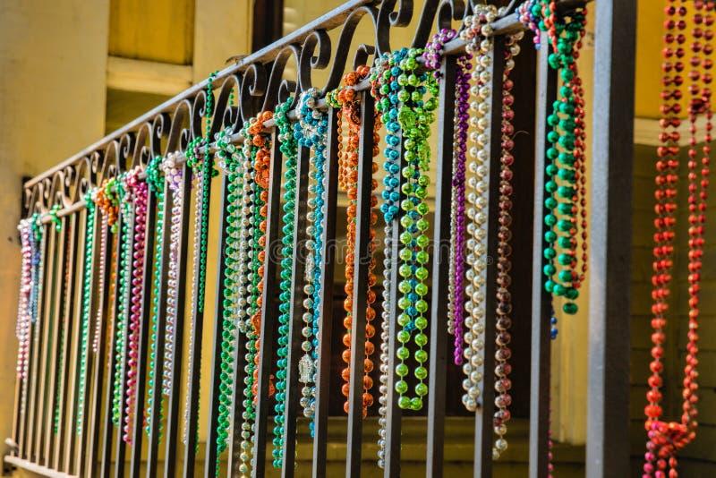 Närbild av Mardi Gras Beads Hanging från en balkong royaltyfri bild