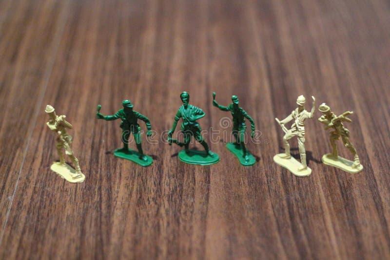 Närbild av miniatyren per gruppen av plast- leksaksoldater på kriget fotografering för bildbyråer