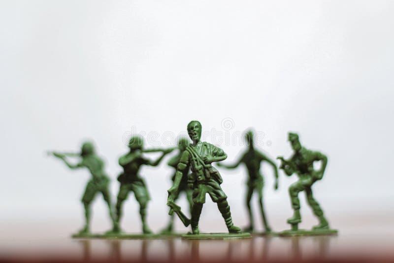 Närbild av miniatyren per gruppen av plast- leksaksoldater på kriget royaltyfri foto