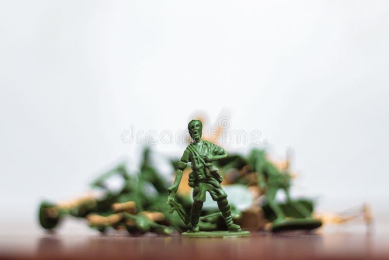 Närbild av miniatyren per gruppen av plast- leksaksoldater på kriget royaltyfria foton