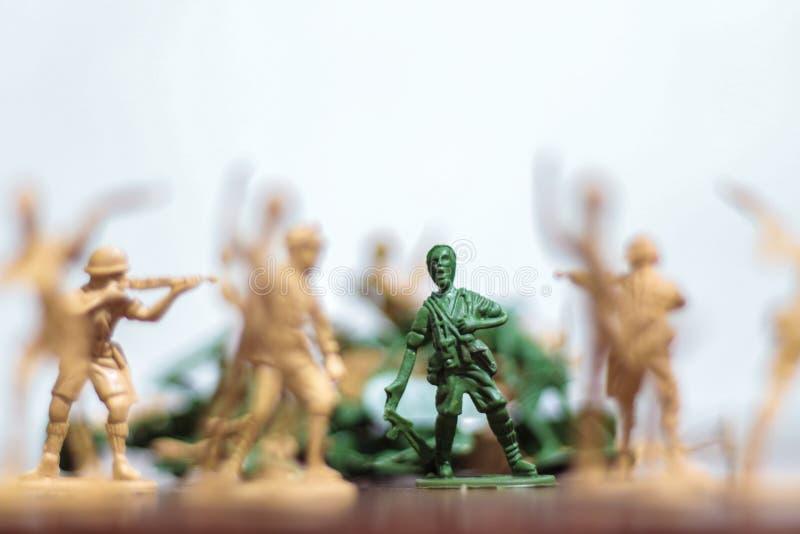 Närbild av miniatyren per gruppen av plast- leksaksoldater på kriget arkivbild
