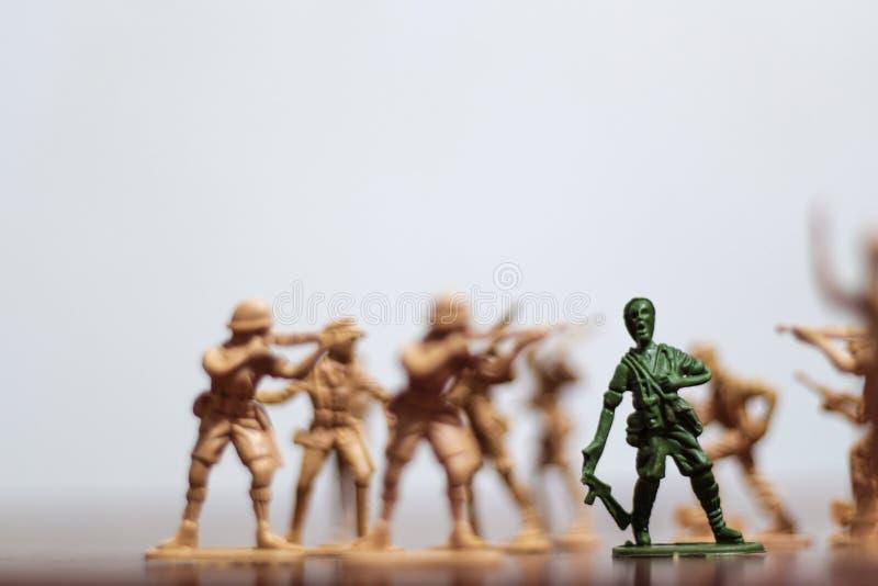 Närbild av miniatyren per gruppen av plast- leksaksoldater på kriget royaltyfria bilder