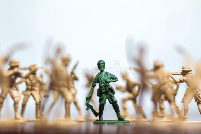 Närbild av miniatyren per gruppen av plast- leksaksoldater på kriget arkivbilder