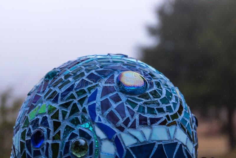 Närbild av mosaikträdgårdbollen i skuggor av blått som göras från målat glasstegelplattor, abstrakt design arkivfoton
