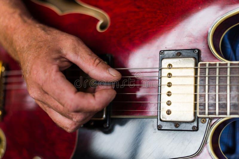 Närbild av någon som spelar gitarren arkivfoto