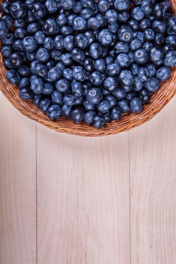 Närbild av nya och ljusa blåbär Sunt, moget, rått och ljust mörker - blåa bär på en träbakgrund kopiera avstånd arkivbild