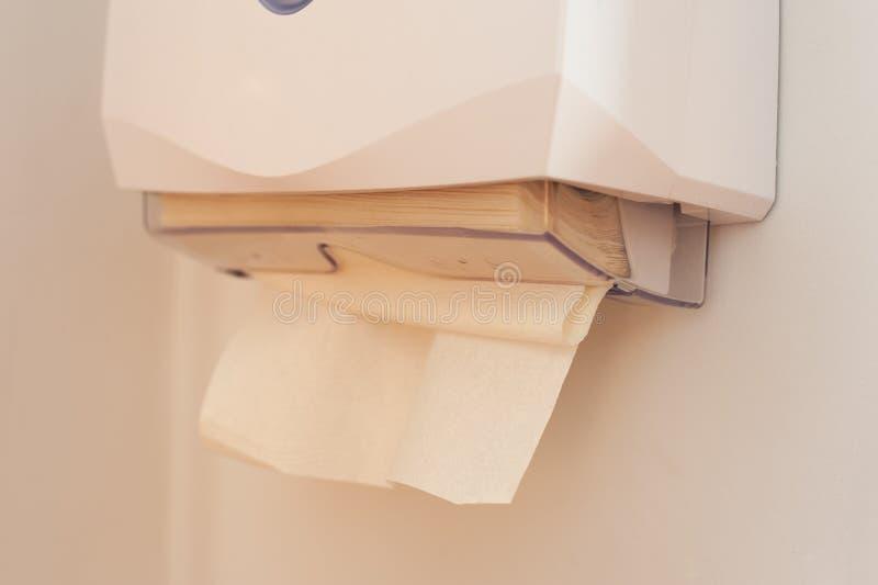 Närbild av pappers- handdukar i en utmatare som hänger på väggen royaltyfri fotografi