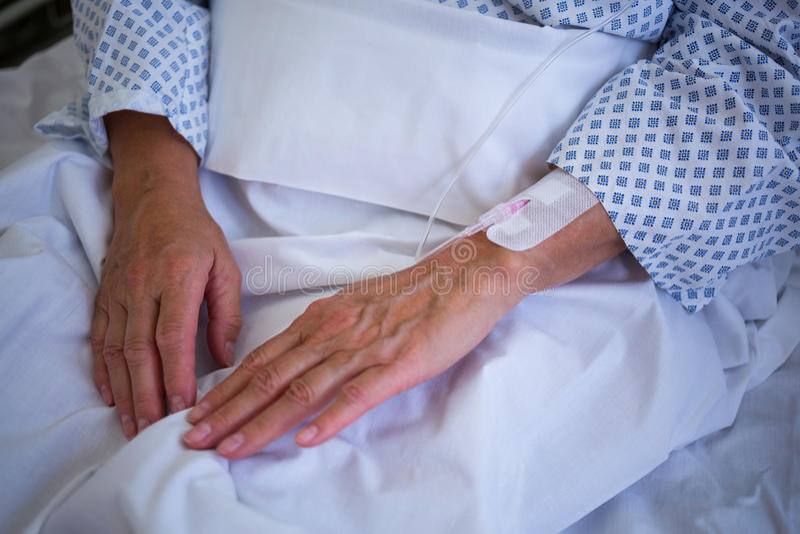 Närbild av patienthanden med iv-droppande arkivfoto