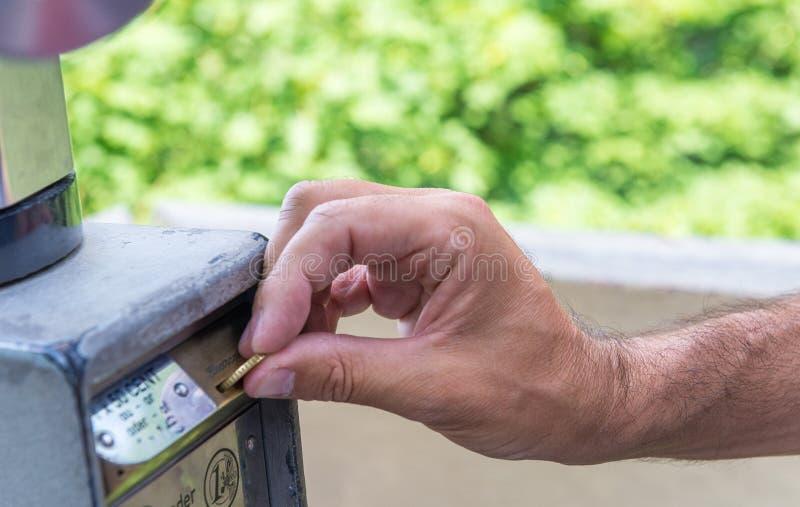 Närbild av persons hand som sätter in biljetten in i parkeringsmaskinen arkivfoto