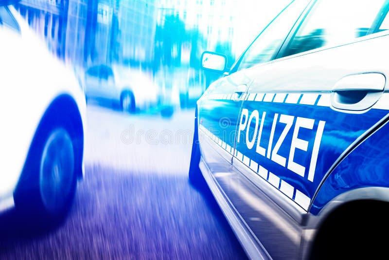 Närbild av polisbilen med att exponera nöd- ljus på den suddiga stads- gatan för rörelse royaltyfri fotografi