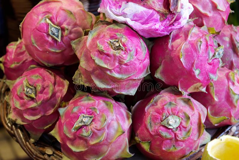 Närbild av röda mogna pitayas eller vita pitahayasdrakefrukter på marknad royaltyfri foto