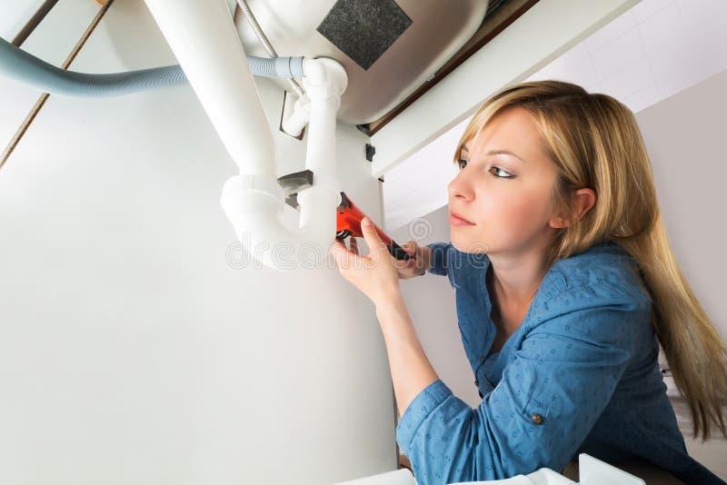 Närbild av röret för kvinnafixandevask med skiftnyckeln arkivbilder
