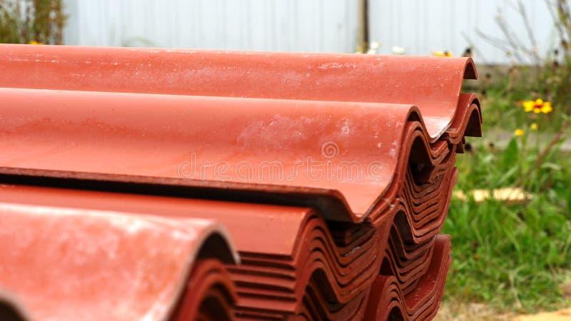 Närbild av rött stål som taklägger att ligga för panelhögar som är utvändigt och förbereds för hus takkonstruktion gem Material o royaltyfri bild