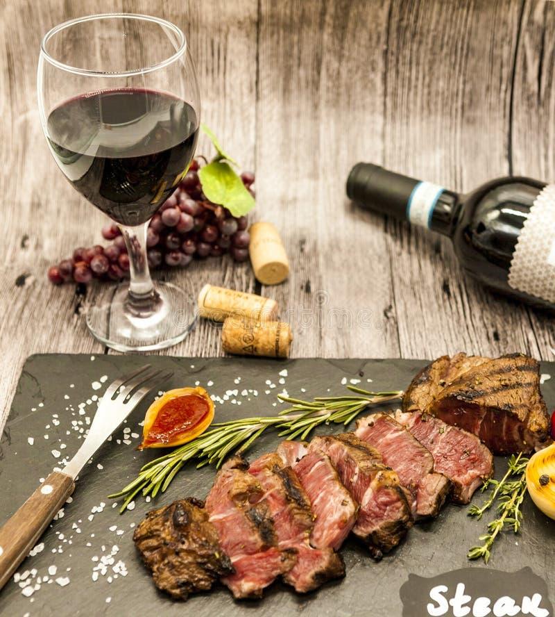 Närbild av saftig striplon för nötköttbiff med en flaska och ett exponeringsglas av rött vin på en svart stenplatta på en trätabe royaltyfri foto