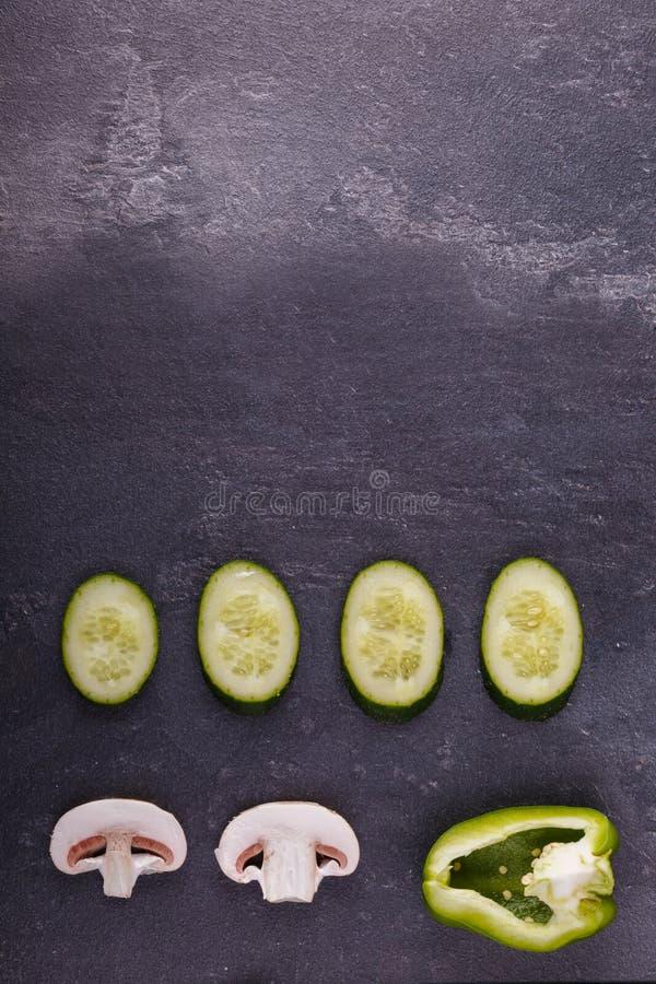 Närbild av skivade, aptitretande sunda grönsaker på en svart bakgrund royaltyfria foton