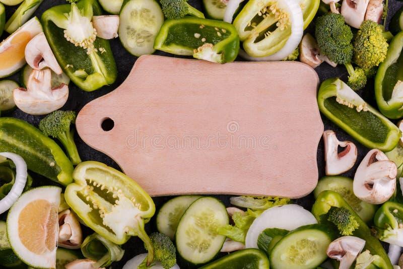 Närbild av skivade grönsaker, broccoli, spansk peppar, skivor av gurkan, champinjoner, limefrukt, lök, i mitt av a royaltyfria foton