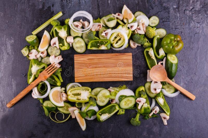 Närbild av skivade grönsaker, i mitt av ett träbräde och anordningar på sidorna på en svart bakgrund royaltyfria foton