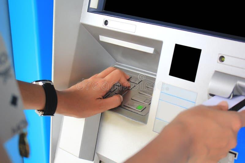 Närbild av skrivande in STIFTnummer för hand med kreditkorten på ATM-bankmaskinen royaltyfri foto