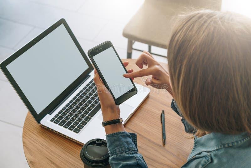 Närbild av smartphonen med den tomma skärmen i händer av sammanträde för ung kvinna på den runda trätabellen och den rörande skär fotografering för bildbyråer