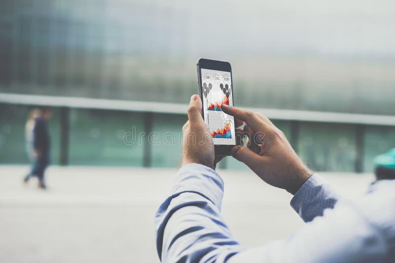 Närbild av smartphonen med grafer, diagram och diagram på skärmen i manliga händer royaltyfri bild