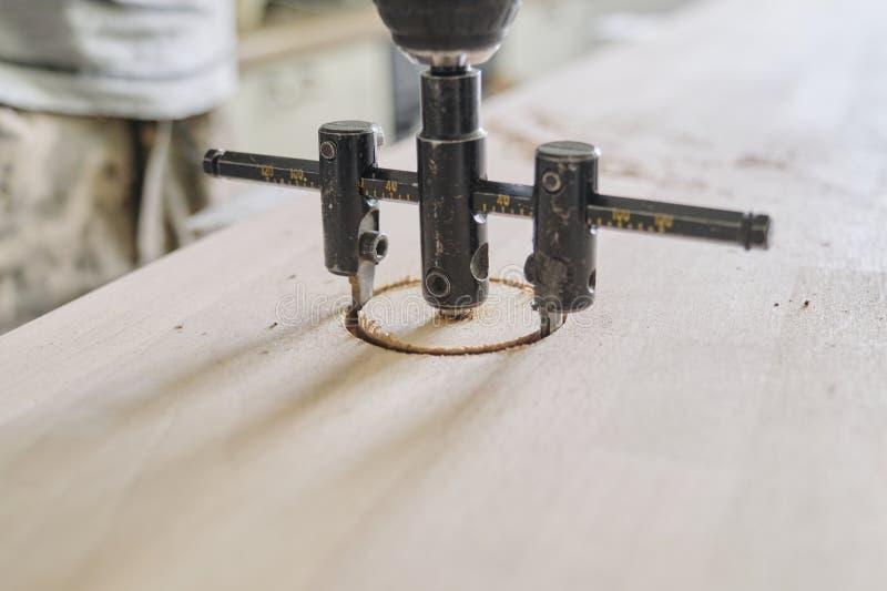 Närbild av snickarehanden genom att använda elektriska hjälpmedel för yrkesmässigt snickeri, när arbeta med trä Manligt snida hål royaltyfri bild