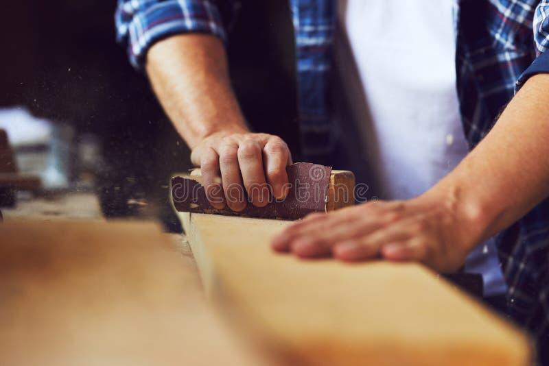 Närbild av snickaren som använder sandpapper på en träplanka fotografering för bildbyråer