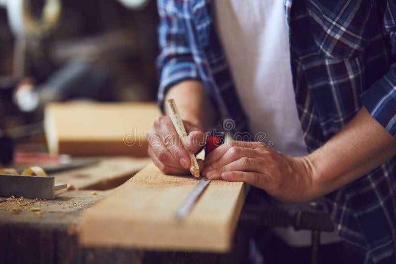 Närbild av snickaren som mäter en träplanka royaltyfri foto