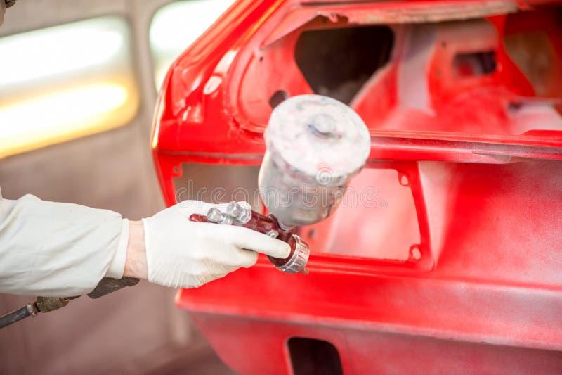 Närbild av sprutmålningsfärgvapnet som målar en röd bil arkivfoton