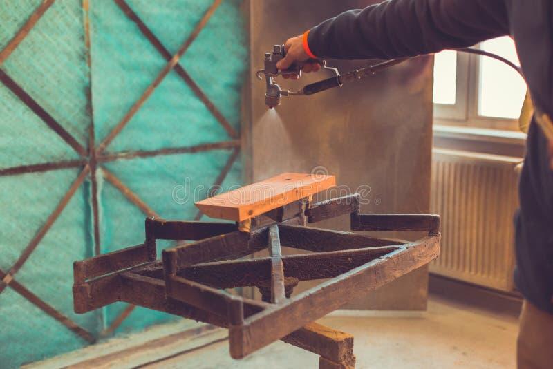 Närbild av sprutpistolen som får målarfärg över timmer Ung målare som renoverar, man som använder skyddande handskar som målar tr arkivfoto