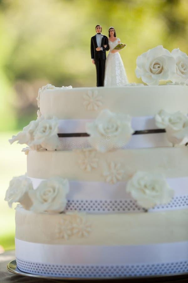 Närbild av statyettpar på bröllopstårtan arkivfoto