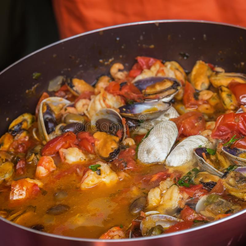 Närbild av stekpannan med den havs- maträtten som lagas mat i tomatsås Ny kokt musslor, räkor, musslor och tioarmad bläckfisk, gr royaltyfri bild