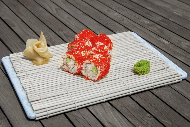 Närbild av sushi och rullar i restaurangköket kokkonst traditionella stekte japanska r?kor Kalifornien sushirullar på bambu som d royaltyfria bilder