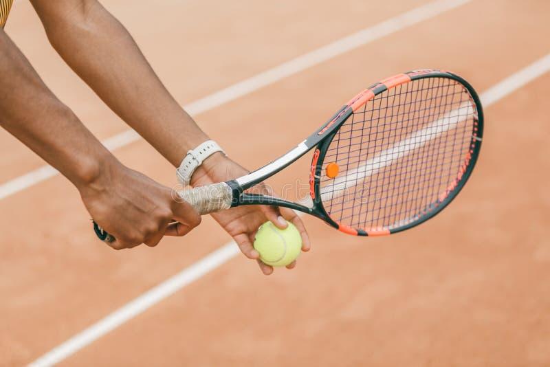 Närbild av tennisbollen och racket för manlig hand den hållande royaltyfria bilder
