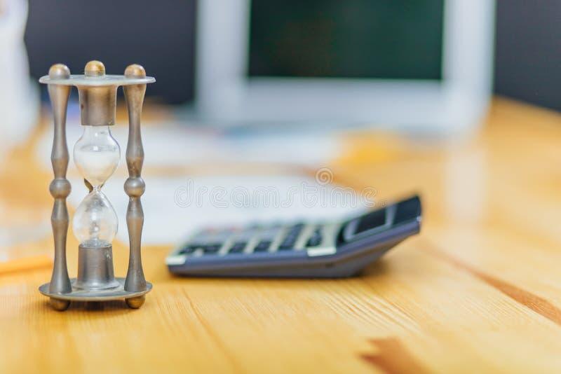 Närbild av timglaset framme av businesspersons hand som beräknar fakturan genom att använda räknemaskinen royaltyfri fotografi