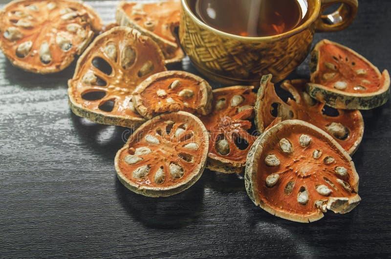 Närbild av torr och glass te för bael och baelfruktsaft på trägolvet arkivfoton