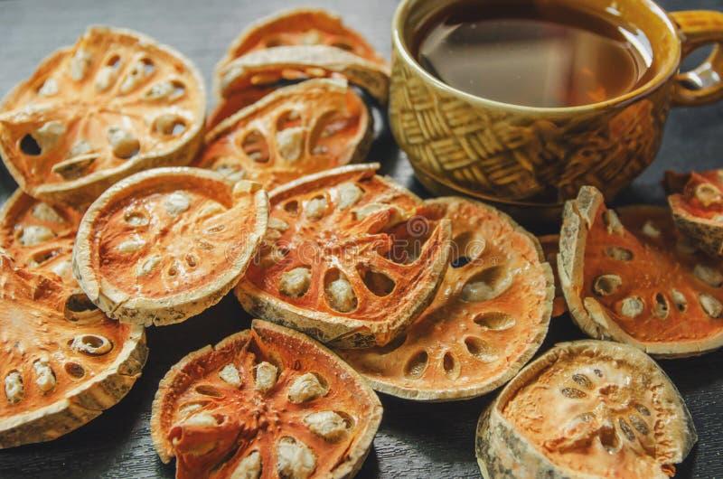 Närbild av torr och glass te för bael och baelfruktsaft på trägolvet arkivbilder