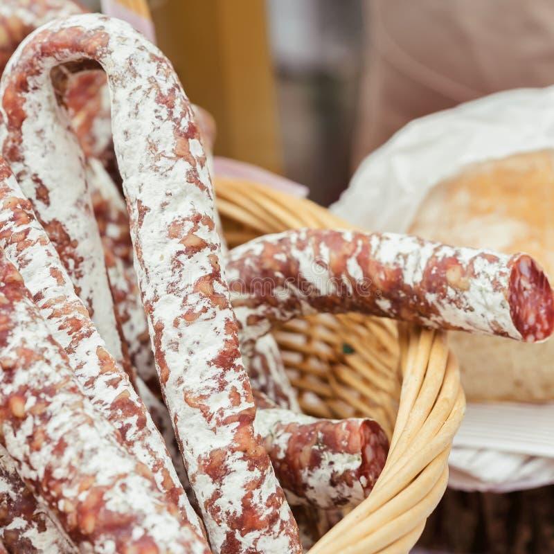 Närbild av traditionella italienska smakliga läckerheter i den vide- korgen, picant organisk salami i marknaden gastronomiskt arkivfoto
