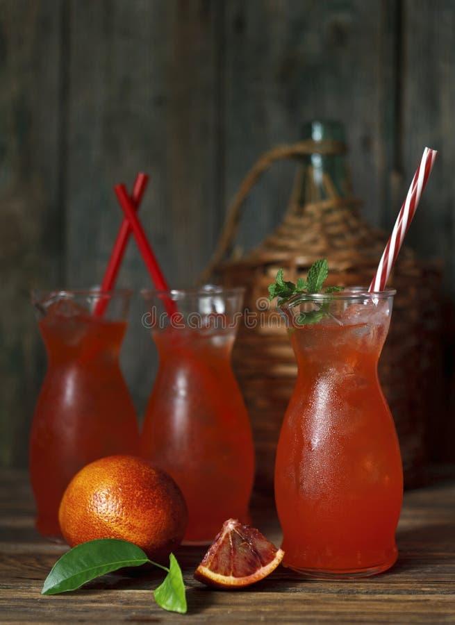 Närbild av tre exponeringsglas med ny hemlagad fruktsaft av en blodig apelsin med is och mintkaramellen på tappningen träbakgrund royaltyfria bilder
