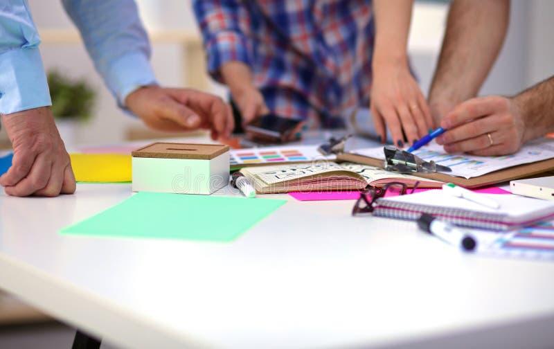 Närbild av tre unga idérika formgivare som tillsammans arbetar på projekt team arbete arkivbild