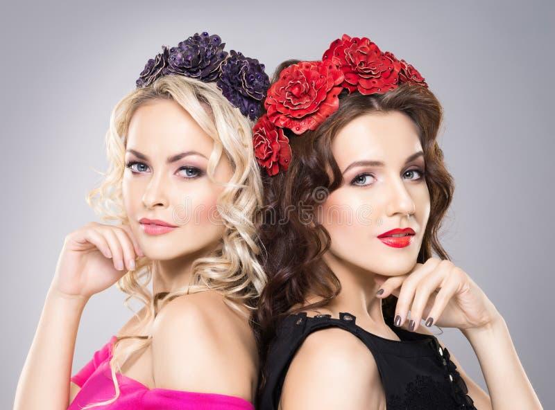 Närbild av två härliga damer som bär blommahuvudbindlar royaltyfria bilder