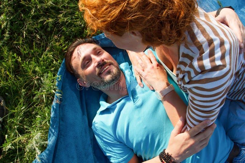 Närbild av unga romantiska par på den soliga dagen i parkera Den glade mannen och kvinnan kramar, medan ha picknicken på äng Dem  arkivfoto