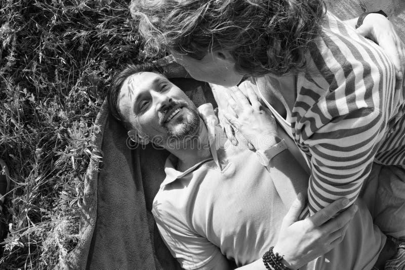 Närbild av unga romantiska par på den soliga dagen i parkera Den glade mannen och kvinnan kramar, medan ha picknicken på äng dem royaltyfri fotografi