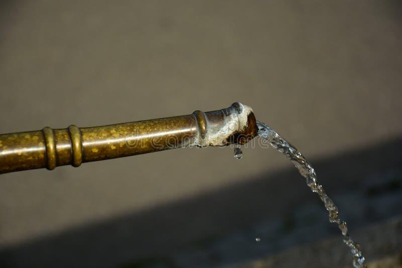 Närbild av vattenspring från utomhus- koppar väl med limescal royaltyfri foto