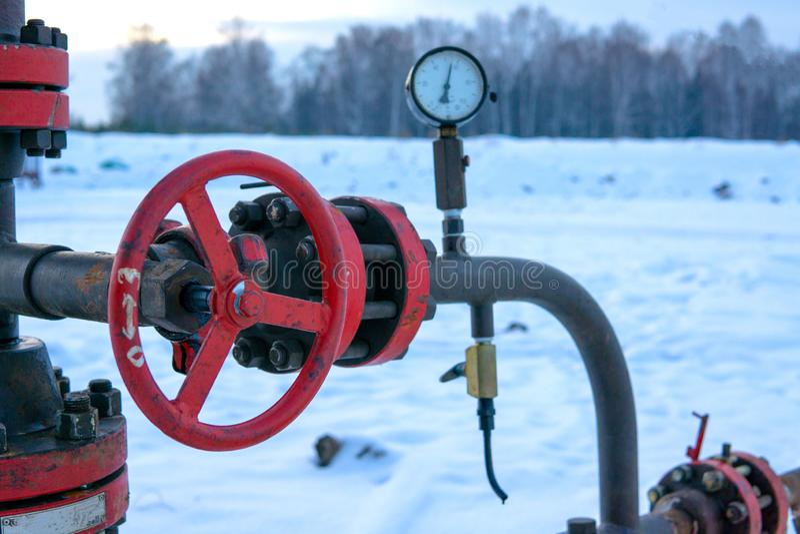 närbild av ventilproppen en oljarörledning i fältet på en solig dag Olje- ventil med att vagga i bakgrunden H?rligt slut royaltyfri fotografi